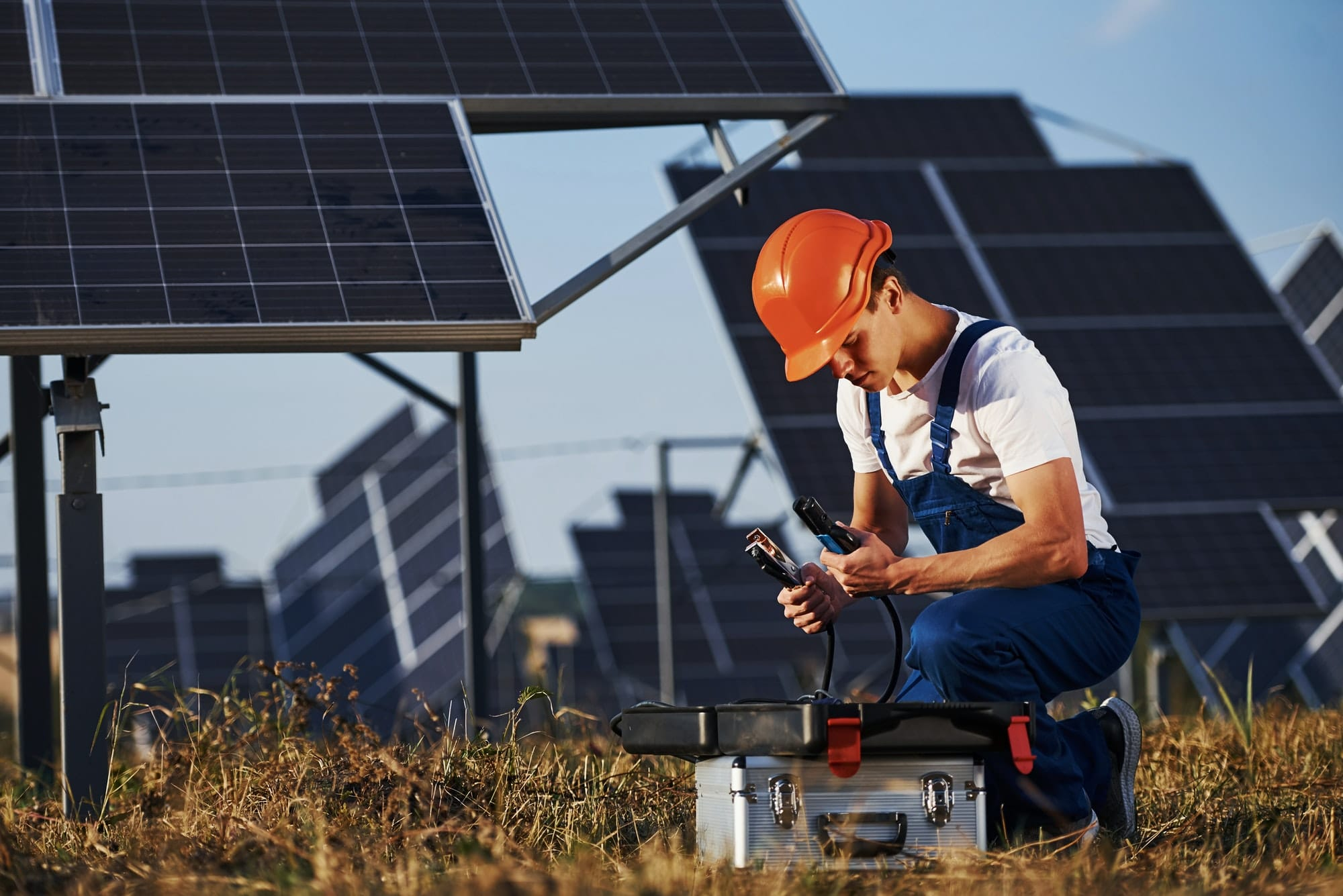 Male worker in blue uniform outdoors with solar batteries at sunny day